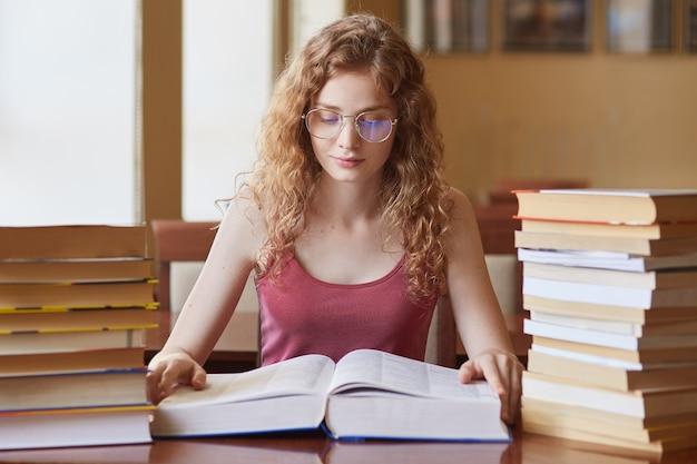 Portret van hardwerkende nadenkende student met mooi krullend haar die enorm boek leest, onderzoek doet, haar lessen voorbereidt, aandachtig kijkt, veel taken moet doen