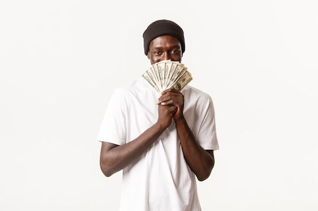 Portret van hebzuchtige, sluwe afro-amerikaanse jonge man die tevreden kijkt met een zelfvoldaan gezicht terwijl hij geld vasthoudt