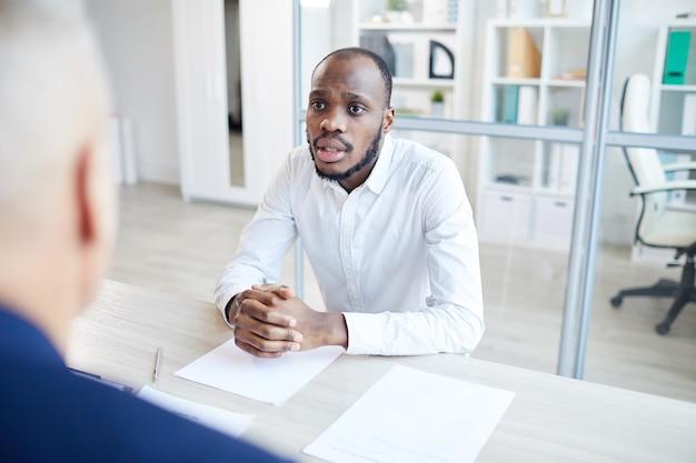 Portret van hedendaagse afro-amerikaanse man beantwoorden van vragen aan hr-manager tijdens sollicitatiegesprek in kantoor, kopie ruimte