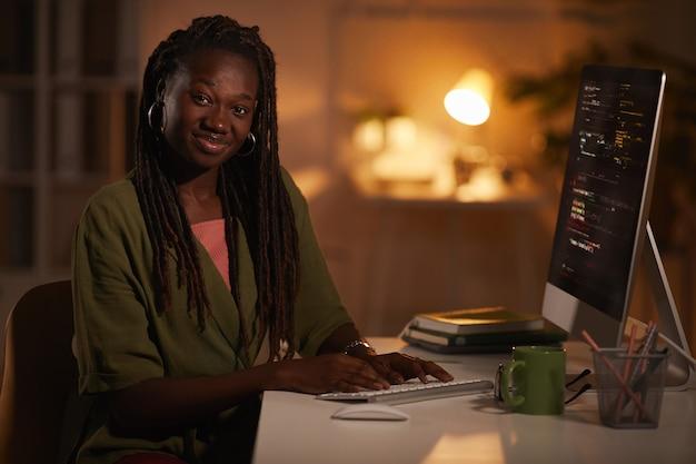 Portret van hedendaagse afro-amerikaanse vrouw code schrijven en camera kijken tijdens het werken in een donkere kantoor, kopieer ruimte