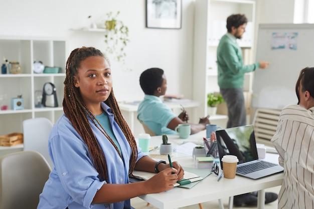Portret van hedendaagse afro-amerikaanse vrouw zittend aan tafel tijdens ontmoeting met creatieve business team