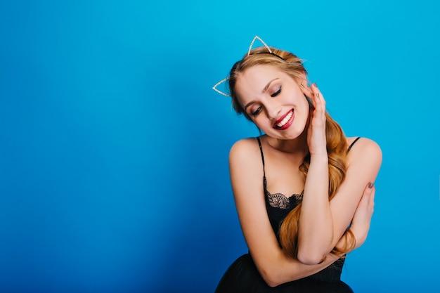 Portret van heel mooi meisje dat sensueel naar beneden kijkt, glimlachend op feestje. ze heeft een zachte huid, lang haar. diadeem met mooie kattenoren met diamanten.