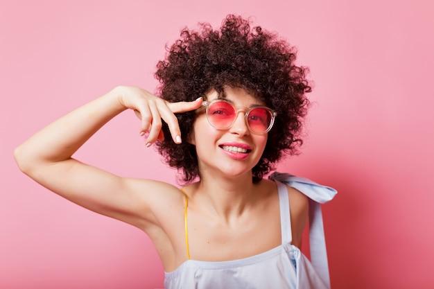 Portret van heldere vrouw met korte krullen draagt roze bril en blauw shirt op roze