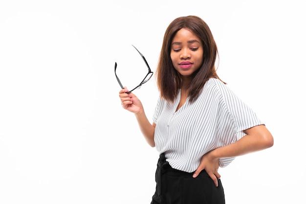 Portret van het aantrekkelijke jonge afro-amerikaanse meisje stellen met glazen op achtergrond