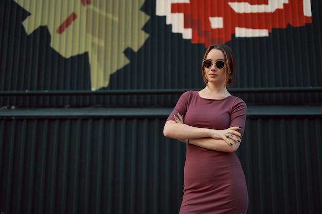 Portret van het aantrekkelijke jonge vrouw stellen tegen donkere muur