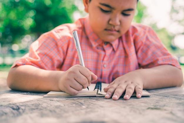 Portret van het aziatische jongen schrijven in agenda in het groene park openlucht