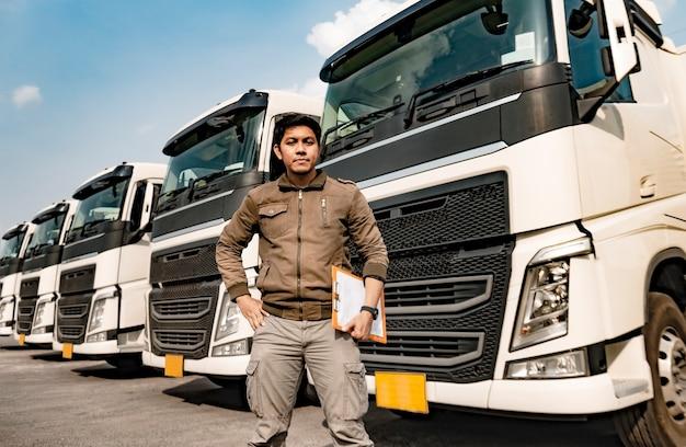 Portret van het aziatische klembord van de vrachtwagenchauffeurholding het inspecteren controlelijst van het veiligheidsvoertuigonderhoud een semi vrachtwagen