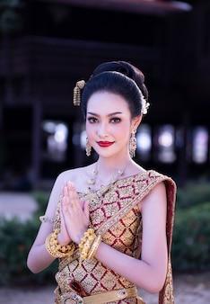 Portret van het aziatische mooie traditionele kostuum die van vrouwenthailand zich openlucht tegen huis bevinden