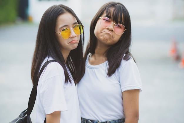 Portret van het aziatische tiener twee ontspannen met geluk in groen park
