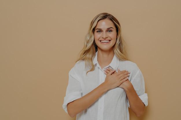 Portret van het bewonderen van schattige vrouw verliefd op blond haar hand in hand op de borst zuchtend met een romantische glimlach, starend naar de camera als dankbaar en waarderend geïsoleerd op beige achtergrond