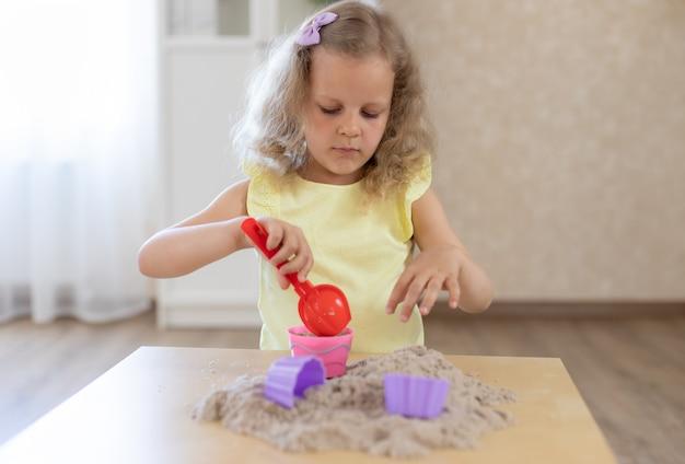 Portret van het blonde meisje spelen met kinetisch zand thuis