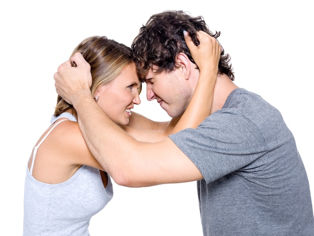 Portret van het boze jonge paar dat over witte achtergrond wordt geïsoleerd