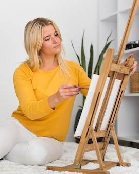 Portret van het casual vrouw schilderen thuis