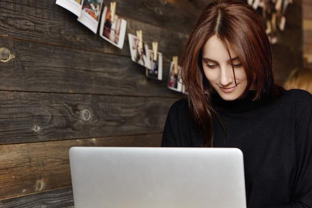 Portret van het charmante jonge donkerbruine vrouwelijke toetsenbord intikken op laptop computer terwijl het zitten alleen bij koffie. intelligent studentenmeisje die aan generische notitieboekjepc werken na haar lezingen aan universiteit
