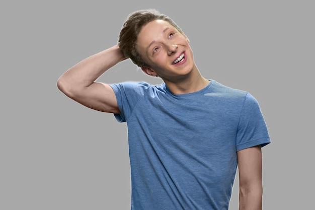 Portret van het dagdromen van de tienerkerel. gelukkig denkende tiener tegen een grijze achtergrond. adolescente man met een doordachte uitdrukking.
