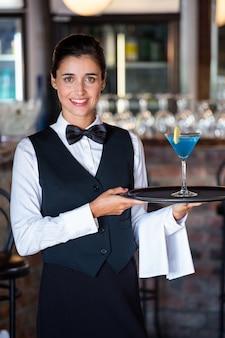 Portret van het dienende dienblad van de barmanholding met glas van cocktail