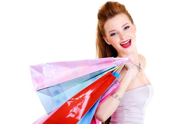 Portret van het gelukkig lachende meisje met aankopen in handen na een wandeling in de winkel