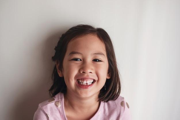 Portret van het gelukkige aziatische jonge meisje glimlachen