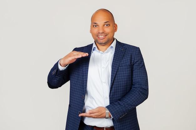 Portret van het gelukkige jonge afrikaanse amerikaanse zakenmankerel gebaren met handen die groot en groot grootteteken, symbool van maatregel tonen.