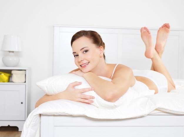 Portret van het gelukkige jonge mooie vrouw ontspannen liggend op bed