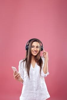 Portret van het gelukkige jonge mooie vrouw stellen geïsoleerd over roze muur