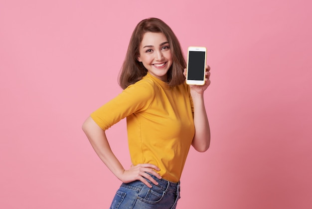 Portret van het gelukkige jonge vrouw tonen bij het lege scherm mobiele telefoon die over roze wordt geïsoleerd.