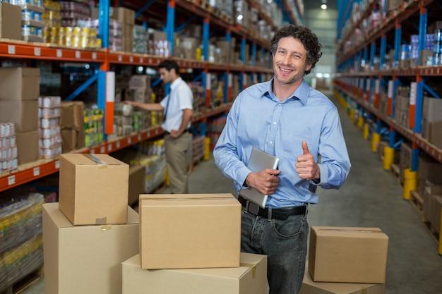 Portret van het gelukkige manager stellen in het midden van kartondozen met omhoog duimen