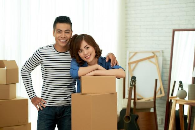 Portret van het gelukkige paar stellen bij pakketdozen vóór verhuizing naar het nieuwe appartement