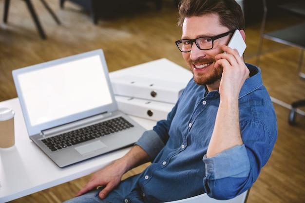 Portret van het gelukkige uitvoerende spreken op cellphone op creatief kantoor