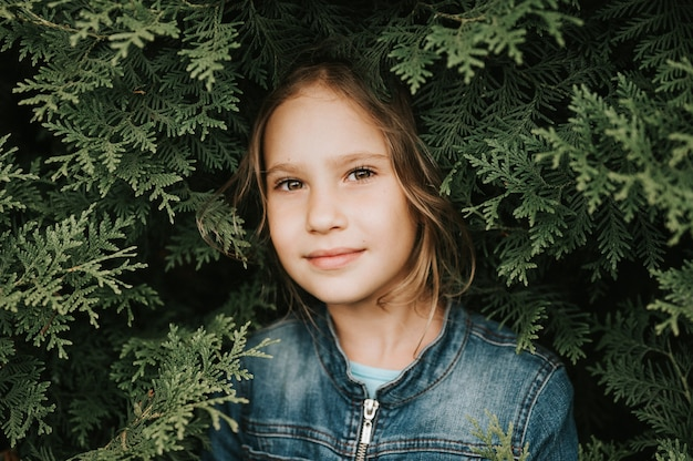 Portret van het gezicht van een schattig gelukkig kaukasisch openhartig gezond achtjarig meisje omringd door takken en bladeren van groene plant thuja of cipres op de natuur buiten