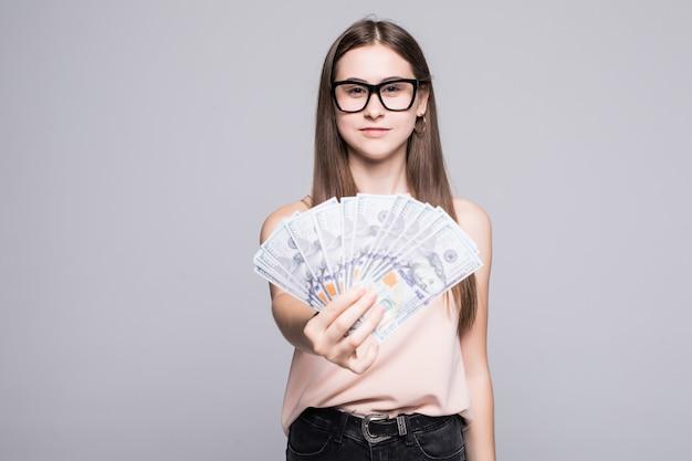 Portret van het glimlachen de dollars van de vrouwenholding over grijze muur worden geïsoleerd die