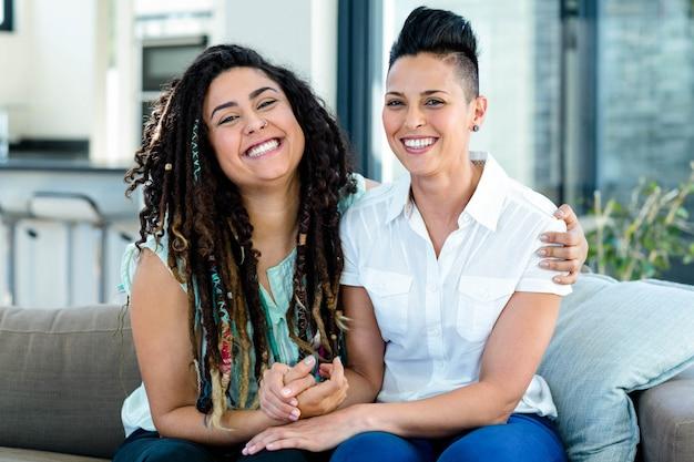 Portret van het glimlachen lesbische paarzitting samen op bank in woonkamer