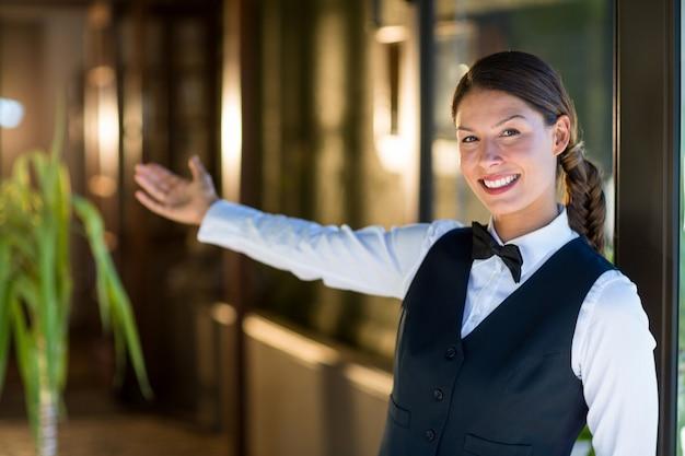 Portret van het glimlachen serveerster het welkom heten