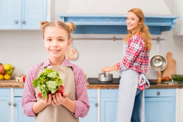 Portret van het glimlachen van de radijs en de spinazie van de meisjesholding ter beschikking met haar moeder bij achtergrond