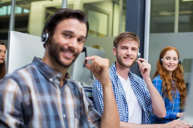 Portret van het glimlachen van de uitvoerende die van de klantendienst op hoofdtelefoon bij bureau spreken