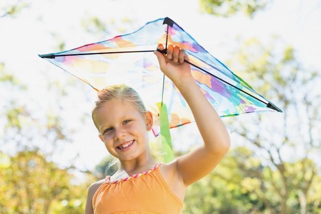 Portret van het glimlachen van de vlieger van de meisjesholding in park