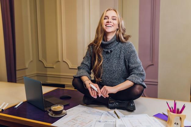 Portret van het glimlachen vrouwelijke binnenlandse ontwerperzitting bij bureau.