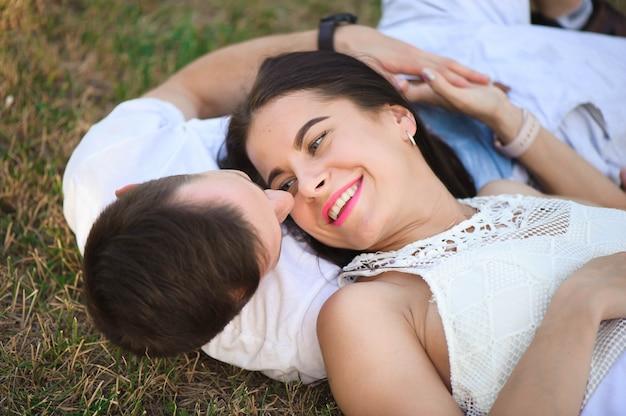 Portret van het jonge aanbiddelijke paar in liefde die hoofd aan kop in openlucht liggen
