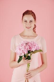 Portret van het jonge aantrekkelijke roodharige vrouw stellen met roze bloeiende bloem