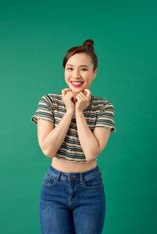Portret van het jonge aziatische meisje stellen over groen.