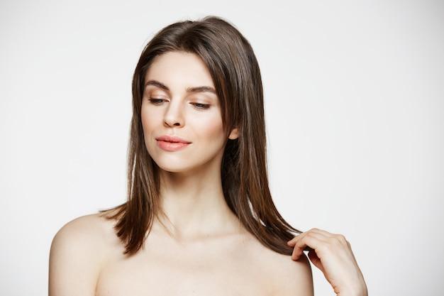 Portret van het jonge donkerbruine mooie vrouw glimlachen wat betreft haar. spa schoonheid gezond en cosmetologie concept.