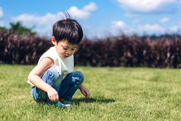 Portret van het jonge gelukkige leuke jongenskind genieten van en speel in aard
