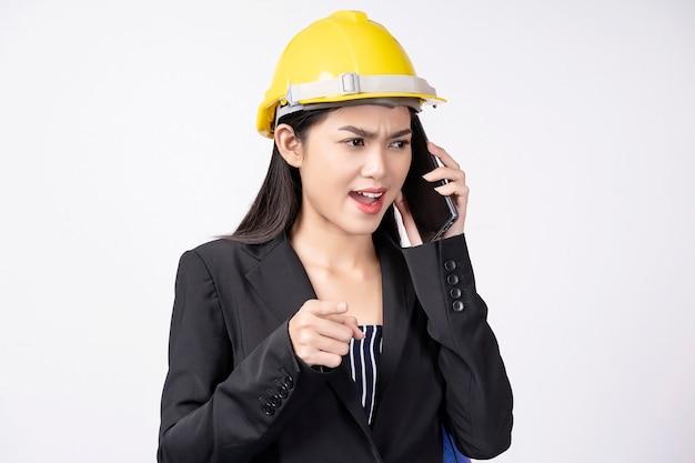 Portret van het jonge ingenieursvrouw gebruiken mobiel met ernstig het spreken