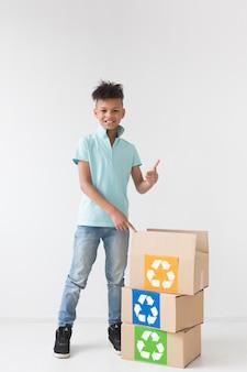 Portret van het jonge jongen stellen met recyclingsdozen