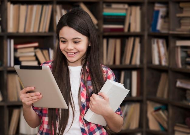 Portret van het jonge meisje spelen op tablet bij de bibliotheek