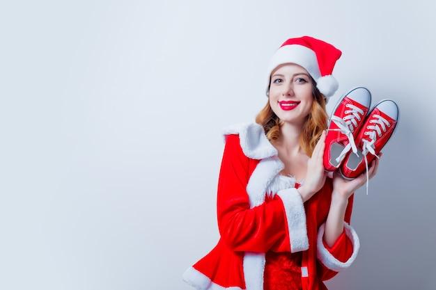 Portret van het jonge meisje van santa clous in rode kleren met gumshoes