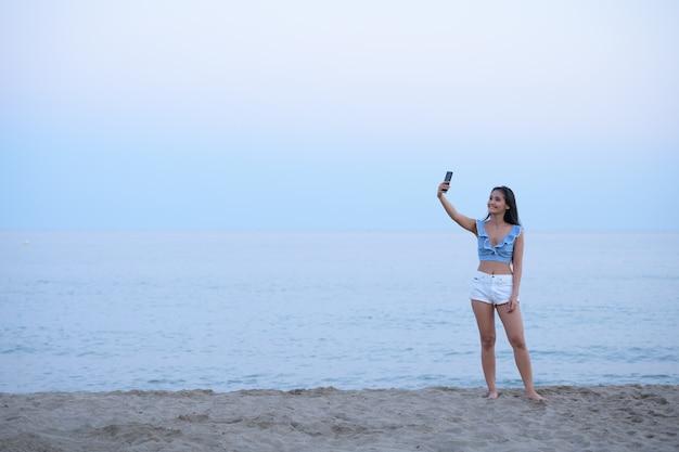 Portret van het jonge mooie aziatische toeristenvrouw ontspannen aan het strand