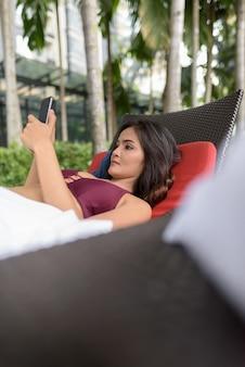 Portret van het jonge mooie aziatische vrouw ontspannen bij zwembad in hotel in kuala lumpur, maleisië