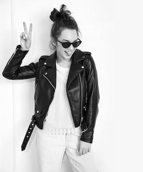 Portret van het jonge mooie donkerbruine model van het vrouwenmeisje met naakte make-up die de kleren van het de leerjasje van de de zomer hipster fietser in zonnebril dragen die dichtbij muur stellen. haar tong en vredesteken tonen