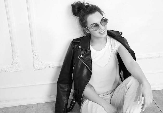 Portret van het jonge mooie donkerbruine model van het vrouwenmeisje met naakte make-up die de kleren van het de leerjasje van de de zomer hipster fietser in zonnebril dragen die dichtbij muur stellen. op de vloer zitten